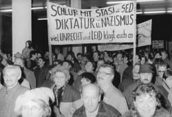 Citizens protesting and entering the Stasi building in Berlin; the sign accuses the Stasi and SED of being Nazistic dictators.